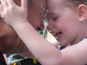 Eine Großmutter wird von ihrem Enkelkind herzlich im Gesicht umarmt. (c) Rita Köhler_pixelio.de