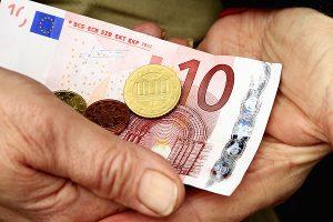 Ein 10 Euro Schein und eine 50 Cent Münze in den Händen einer alten Person. (c) Uschi Dreiucker_pixelio.de