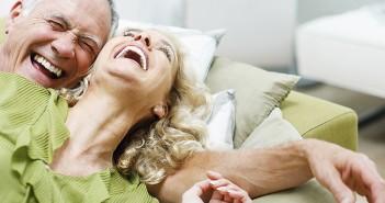 Älteres Paar liegt lachend auf der Couch.