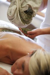 Frau liegt auf einem Massagetisch und bekommt einen Heuwickel. (c) Marienschwestern